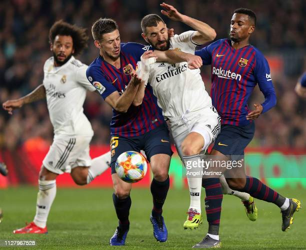 Karim Benzema of Real Madrid competes for the ball with Clement Lenglet and Nelson Semedo of FC Barcelona during the Copa del Rey Semi Final match...