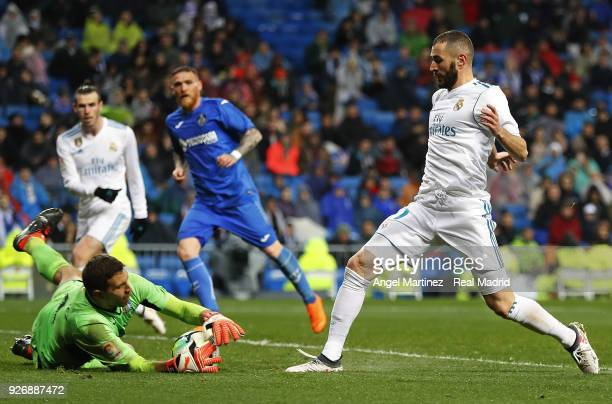 Karim Benzema of Real Madrid competes for the ball with Emiliano Martinez of Getafe during the La Liga match between Real Madrid and Getafe at...