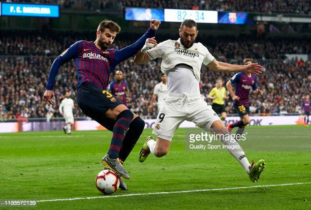 Karim Benzema of Real Madrid competes for the ball with Gerard Pique of Barcelona during the La Liga match between Real Madrid CF and FC Barcelona at...