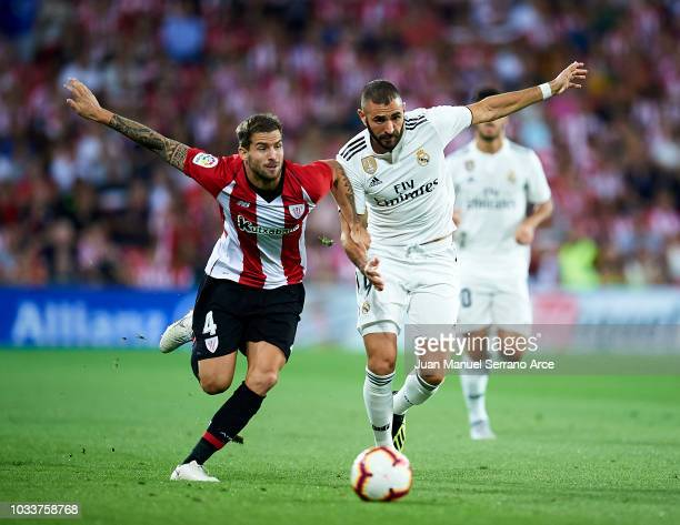 Karim Benzema of Real Madrid competes for the ball with Inigo Martinez of Athletic Club during the La Liga match between Athletic Club Bilbao and...