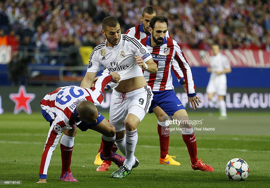 Karim Benzema of Real Madrid competes for the ball with Joao Miranda (L) of Atletico de Madrid during the UEFA Champions League Quarter Final first leg match between Club Atletico de Madrid and Real Madrid CF at Vicente Calderon Stadium on April 14, 2015 in Madrid, Spain.