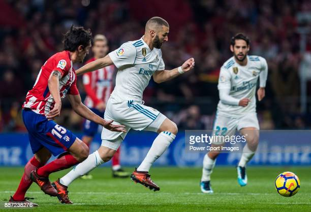 Karim Benzema of Real Madrid competes for the ball with Stefan Savic of Atletico de Madrid during the La Liga 201718 match between Atletico de Madrid...