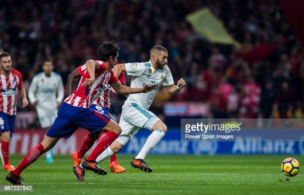 Karim Benzema of Real Madrid competes for the ball with Thomas Teye Partey and Stefan Savic of Atletico de Madrid during the La Liga 201718 match...