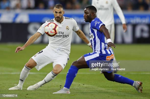 Karim Benzema of Real Madrid competes for the ball with Wakaso Mubarak of Deportivo Alaves during the La Liga match between Deportivo Alaves and Real...