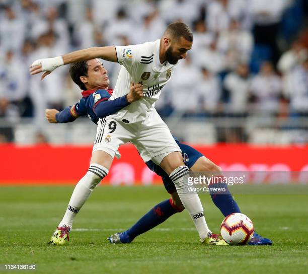 Karim Benzema of Real Madrid competes for the ball with Xabier Etxeita of Huesca during the La Liga match between Real Madrid CF and SD Huesca at...