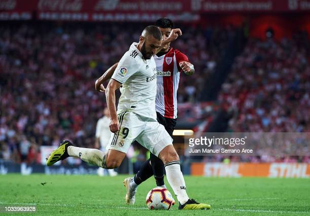 Karim Benzema of Real Madrid competes for the ball with Yuri Berchiche of Athletic Club during the La Liga match between Athletic Club Bilbao and...