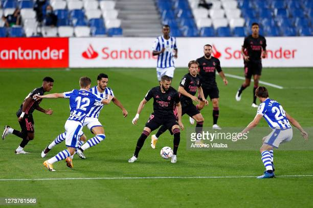 Karim Benzema of Real Madrid controls the ball under pressure from Robin Le Normand and Aihen Munoz of Real Sociedad during the La Liga Santander...