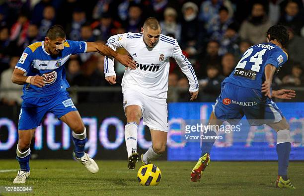 Karim Benzema of Real Madrid fights for the ball with Cata Diaz and Miguel Torres of Getafe during La Liga match between Getafe and Real Madrid at...