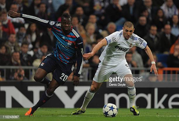 Karim Benzema of Real Madrid gets past Aly Cissokho of Lyon during the UEFA Champions League round of 16 second leg match between Real Madrid and...