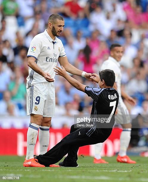 Karim Benzema of Real Madrid helps up a pitch invader during the La Liga match between Real Madrid CF and CA Osasuna at Estadio Santiago Bernabeu on...