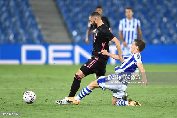 Karim Benzema of Real Madrid is challenged by Aihen Munoz of Real Sociedad during the La Liga Santander match between Real Sociedad and Real Madrid...