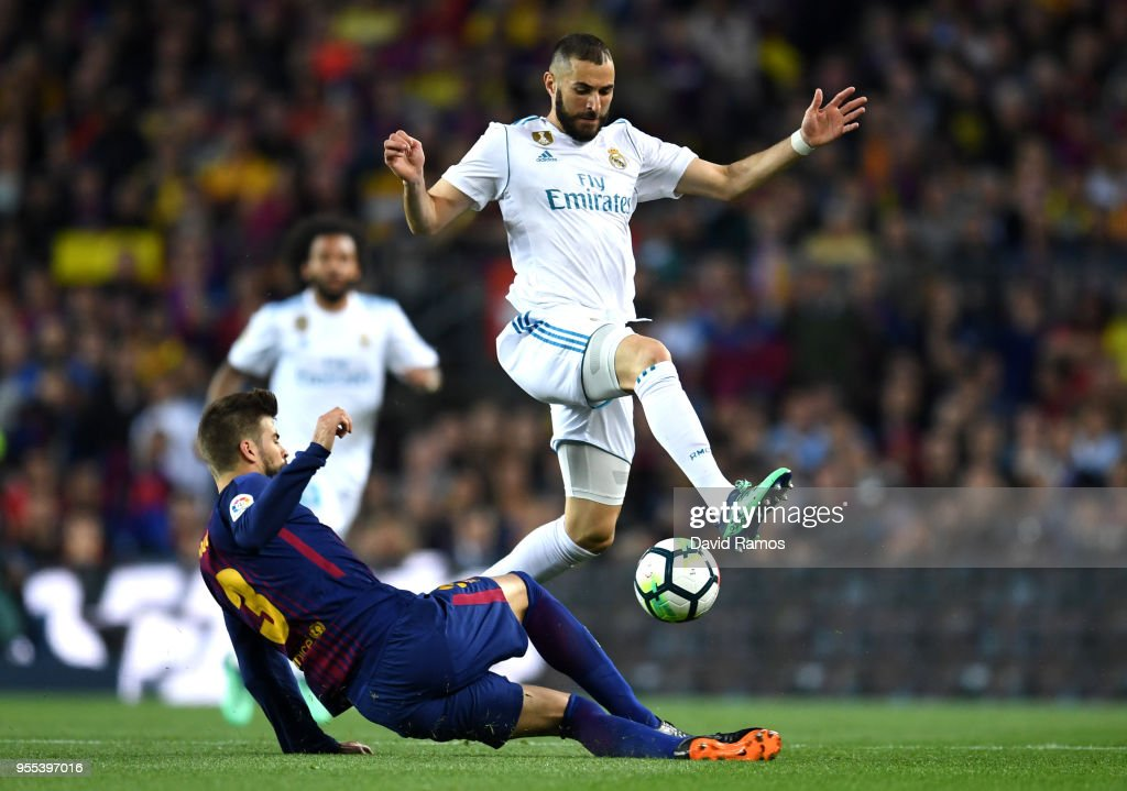 Karim Benzema of Real Madrid is challenged by Gerard Pique of Barcelona during the La Liga match between Barcelona and Real Madrid at Camp Nou on May 6, 2018 in Barcelona, Spain.