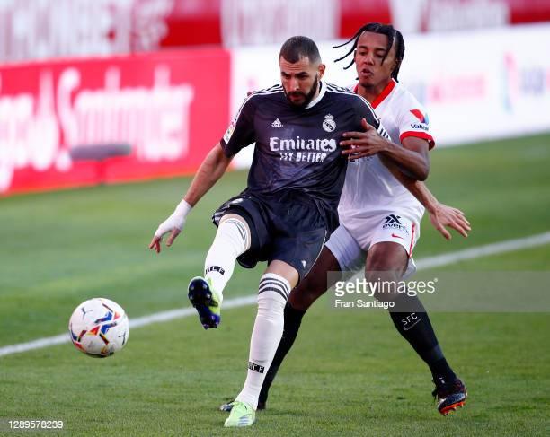Karim Benzema of Real Madrid is challenged by Jules Kounde of Sevilla during the La Liga Santander match between Sevilla FC and Real Madrid at...