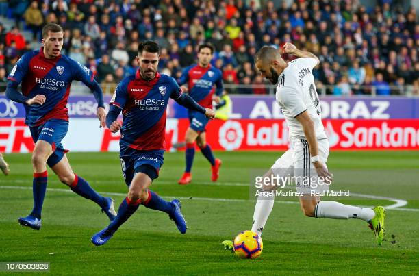 Karim Benzema of Real Madrid is challenged by Pablo Insua of SD Huesca during the La Liga match between SD Huesca and Real Madrid CF at Estadio El...