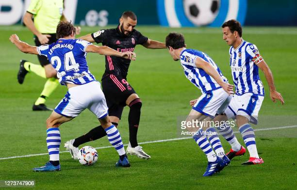 Karim Benzema of Real Madrid is challenged by Robin Le Normand and Aritz Elustondo of Real Sociedad during the La Liga Santander match between Real...