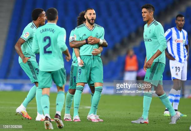 Karim Benzema of Real Madrid is congratulated by team mate Marcelo after scoring his teams second goal during the Liga match between Real Sociedad...