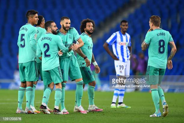 Karim Benzema of Real Madrid is congratulated by team mates after scoring his teams second goal during the Liga match between Real Sociedad and Real...