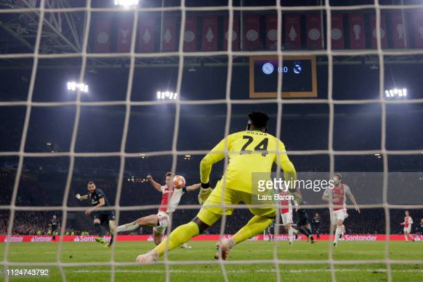 Karim Benzema of Real Madrid scores his team's first goal past Andre Onana of Ajax during the UEFA Champions League Round of 16 First Leg match...
