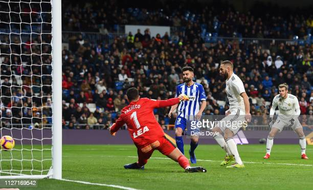 Karim Benzema of Real Madrid scores his team's first goal past Fernando Pacheco of Deportivo Alaves during the La Liga match between Real Madrid CF...