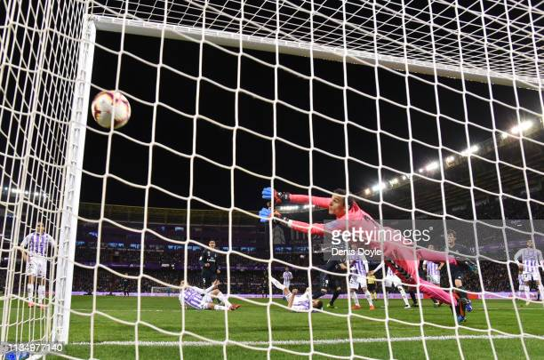 Karim Benzema of Real Madrid scores his team's third goal past goalkeeper Jordi Masip of Real Valladolid during the La Liga match between Real...