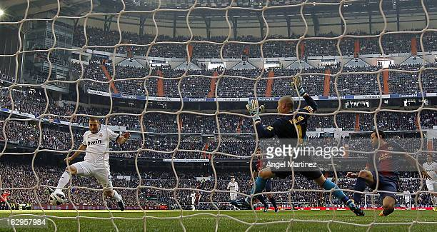Karim Benzema of Real Madrid scores the opening goal past goalkeeper Victor Valdes and Javier Mascherano of Barcelona during the La Liga match...