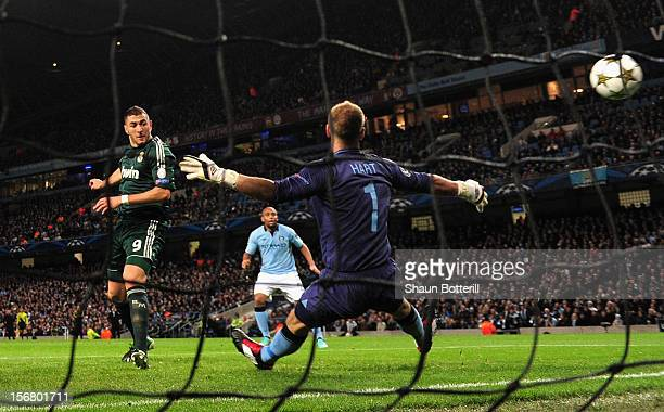 Karim Benzema of Real Madrid scores the opening goal past Joe Hart of Manchester City during the UEFA Champions League Group D match between...