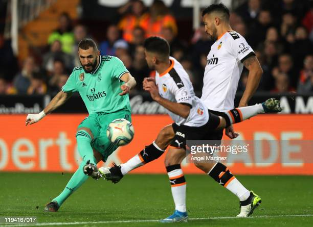 Karim Benzema of Real Madrid shoots on goal past Ezequiel Garay of Valencia during the Liga match between Valencia CF and Real Madrid CF at Estadio...