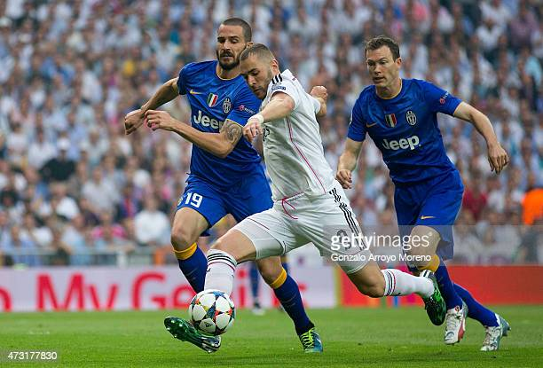Karim Benzema of Real Madrid takes a shot on goal under pressure from Leonardo Bonucci of Juventus during the UEFA Champions League Semi Final second...