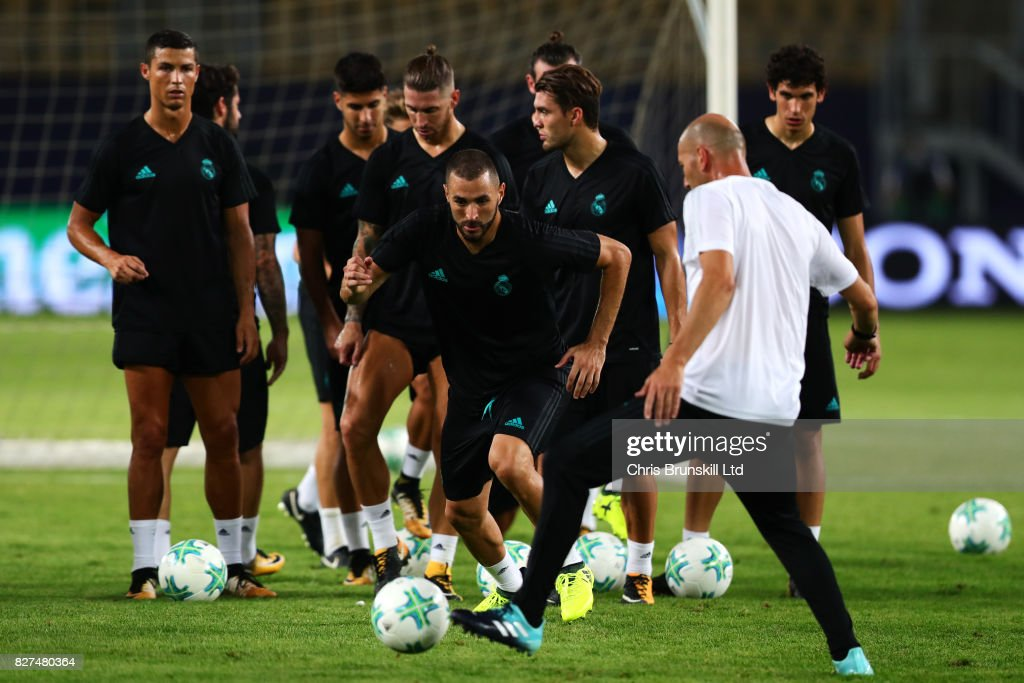 Karim Benzema runs past his manager, Zinedine Zidane, during a Real Madrid training session ahead of the UEFA Super Cup at the National Arena Filip II Macedonian on August 7, 2017 in Skopje, Macedonia.