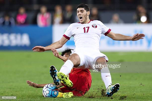 Karim Boudiaf of Qatar falls down onto Wu Xi of China vie for the ball during the 2018 FIFA World Cup Qualifier match between China and Qatar at...