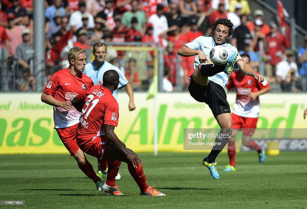 Karim Guede (C) and Mike Hanke (L) of Freiburg battles for the ball with Nicolai Mueller (R) of Mainz during the Bundesliga match between SC Freiburg and FSV Mainz 05 at MAGE SOLAR Stadium on August 17, 2013 in Freiburg im Breisgau, Germany.