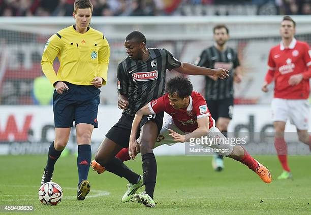 Karim Guede of Freiburg and Shinji Okazaki of Mainz compete for the ball during the Bundesliga match between FSV Mainz 05 and SC Freiburg at Coface...