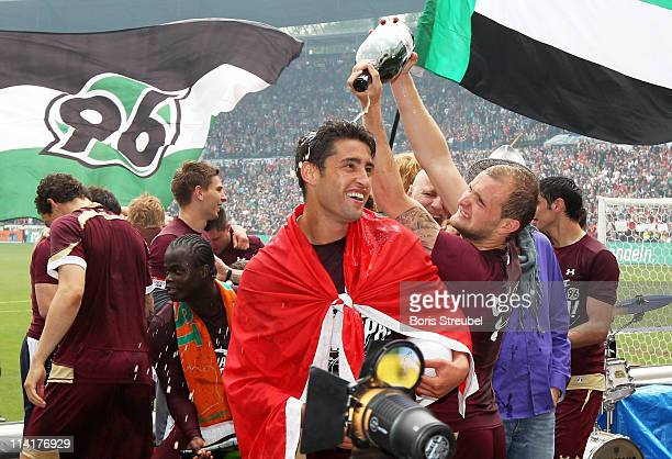Karim Haggui of Hannover gets a champagne shower from Konstantin Rausch after the Bundesliga match between Hannover 96 and 1 FC Nuernberg at AWD...