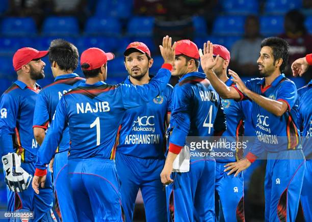 Karim Janat of Afghanistan celebrates with teammates two West Indies wickets during the 2nd T20i match between West Indies and Afghanistan at Warner...