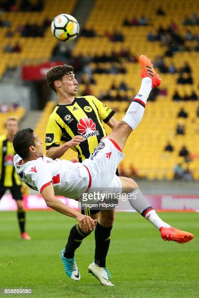 Karim Matmour of Adelaide United performs a bicycle kick in front of Matthew Ridenton of the Phoenix during the round one ALeague match between...