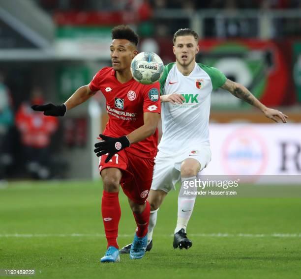 Karim Onisiwo of 1. FSV Mainz 05 is challenged by Jeffrey Gouweleeuw of FC Augsburg during the Bundesliga match between FC Augsburg and 1. FSV Mainz...
