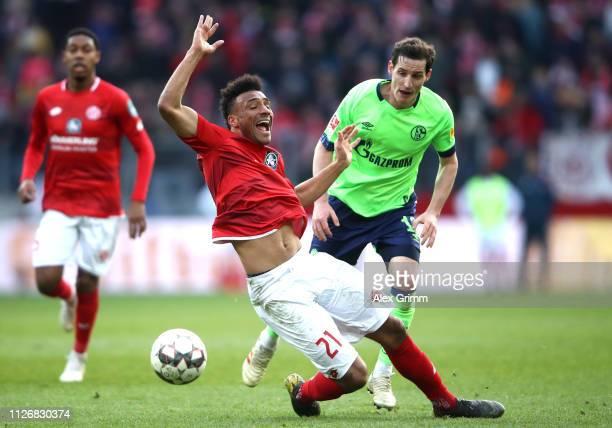 Karim Onisiwo of FSV Mainz is challenged by Sebastian Rudy of FC Schalke 04 during the Bundesliga match between 1 FSV Mainz 05 and FC Schalke 04 at...
