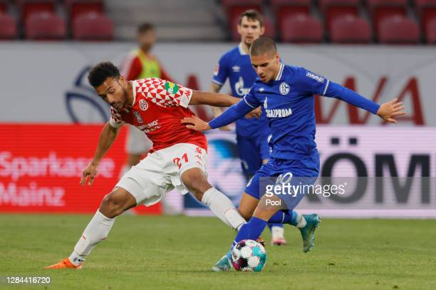 Karim Onisiwo of Mainz is challenged by Can Bozdogan of Schalke during the Bundesliga match between 1. FSV Mainz 05 and FC Schalke 04 at Opel Arena...