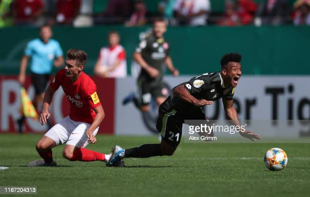 Karim Onisiwo of Mainz is challenged by Carlo Sickinger of Kaiserslautern during the DFB Cup first round match between 1 FC Kaiserslautern and 1 FSV...