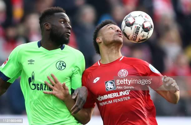 Karim Onisiwo of Mainz is challenged by Salif Sane of Schalke during the Bundesliga match between 1 FSV Mainz 05 and FC Schalke 04 at Opel Arena on...