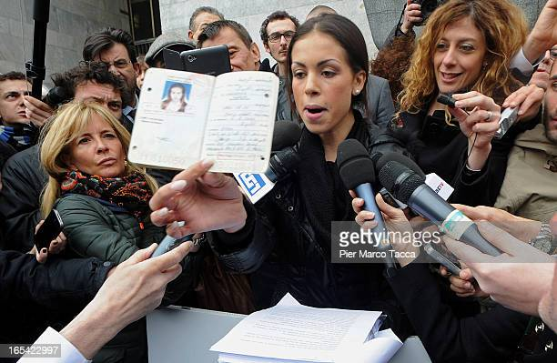 Karima El Mahroug shows her passport to members of the media during a protest in front of Palazzo di Giustizia on April 4 2013 in Milan Italy Karima...
