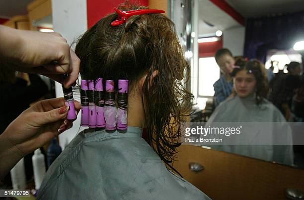 Karima gets her hair permed by a student beautician during the clinic phase where students train on the public at the Kabul Beauty School on October...