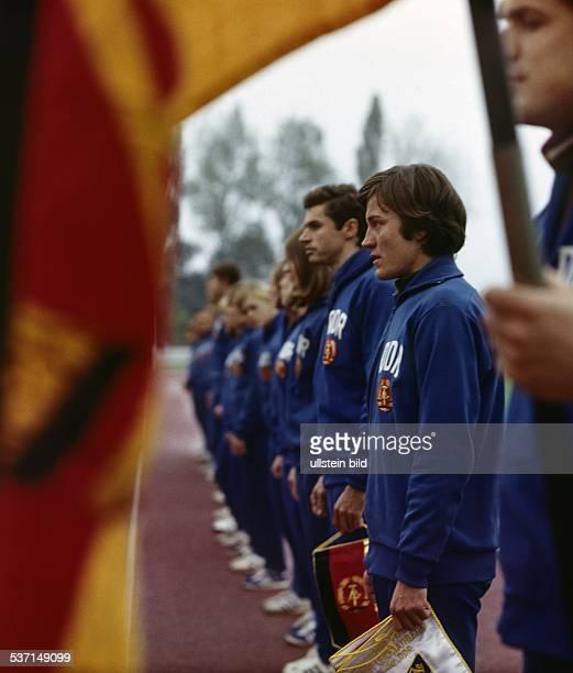 Karin Balzer * Leichtathletin DDR steht vr neben Wolfgang Nordwig und dem Fahnenträger mit der DDRFlagge in einer Reihe von DDRSportlern undatierte...