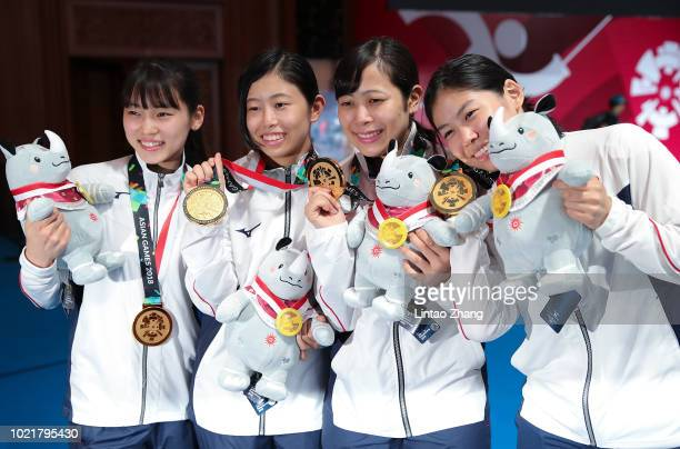 Karin Miyawaki Srea Azura Sumire Tsuji and Karin MiyawakI of Japan pose on the podium during the awards ceremony after winning against team of China...