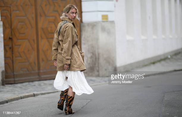 Karin Teigl wearing H&M jacket and dress, DIOR boots and bag on March 25, 2019 in Augsburg, Germany.