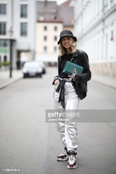 Karin Teigl wearing Isabel Marant pants, Balenciaga Triple S sneaker, Christian Dior belt, Saint Laurent bag, andotherstories hat and Dior jacket on...