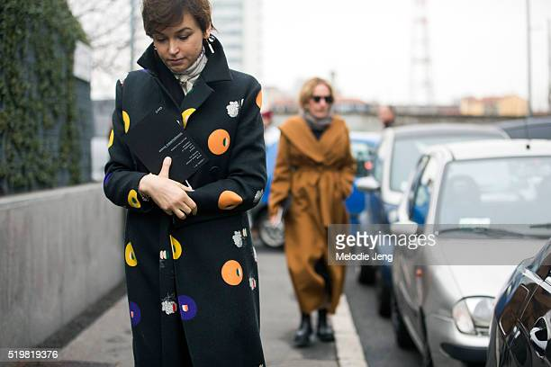 Karina Dobrotvorskaya of Conde Nast attends the Bottega Veneta show in a black coat with a print pattern during the Milan Fashion Week Fall/Winter...