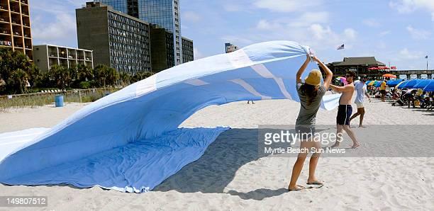 Karina Golkova David Shreve and Alan Gutierrez unfold the giant beach towel created by Miamibased performance artist Misael Soto Measuring 56x29 feet...
