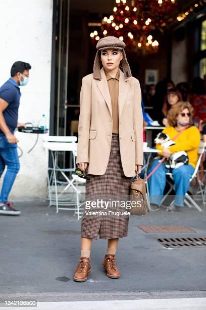 Karina Nigay outside Max Mara fashion show wearing hat, beige blazer, checkered skirt, button shirt, bag during the Milan Fashion Week - Spring /...