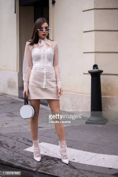 Karina Nigay wearing a cream lace shirt cream skirt white bag and white decorated heels is seen outside Elie Saab on Day 6 Paris Fashion Week...